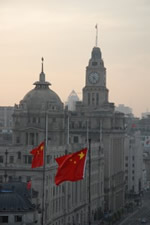 A towered building in China with national Chinese flags in the foreground